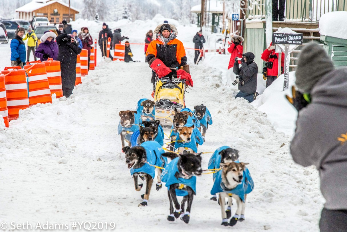 Sled dog team and musher in orange parka run down snowy chute.