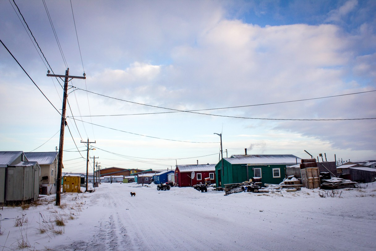 Snow-covered, rural Alaska street on a partly cloudy winter day.