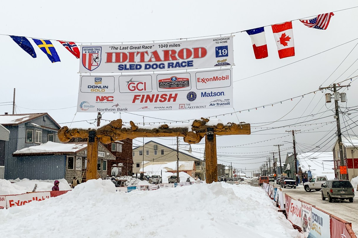 "Looking down a snow-covered street in a rural Alaska town with a large ""Iditarod"" banner hanging overhead and a carved wooden archway standing in the center of the street."
