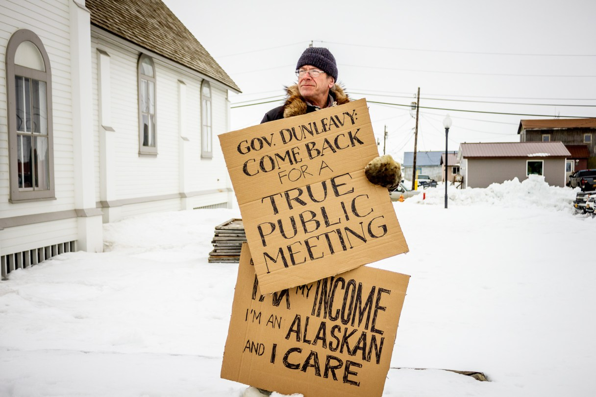 Man holding cardboard protest signs outside Nome community hall