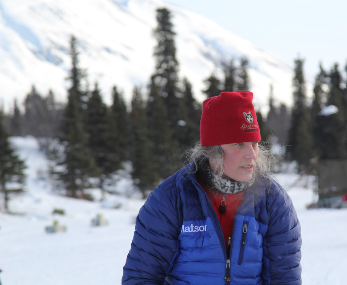 Woman in blue and purple parka with red hat