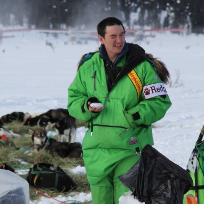 Man in bright green parka stands in front of a sled dog team resting on the ground.