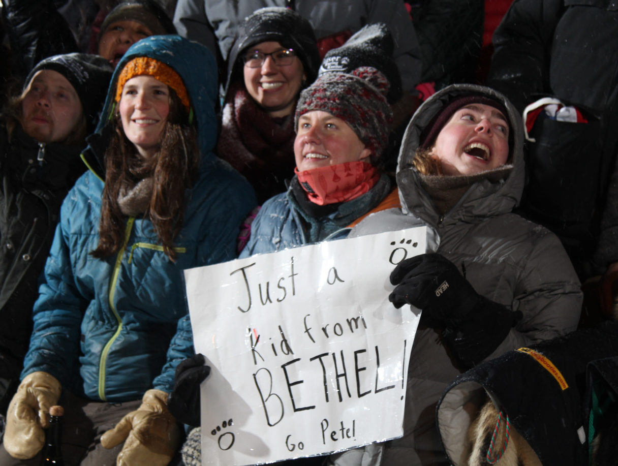 "Iditarod race fan holding sign reading ""Just a kid from Bethel."""