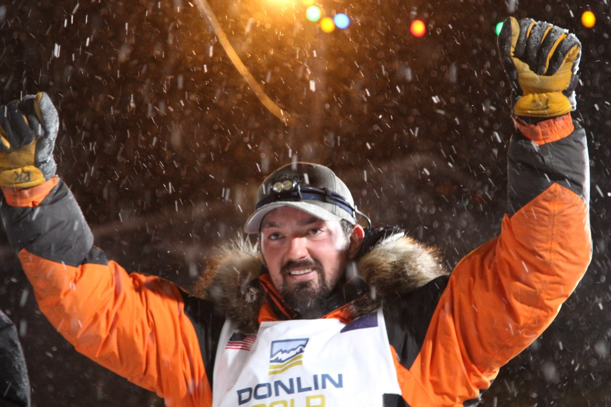 Man in orange and black parka raises his hands in triumph after his Iditarod victory.