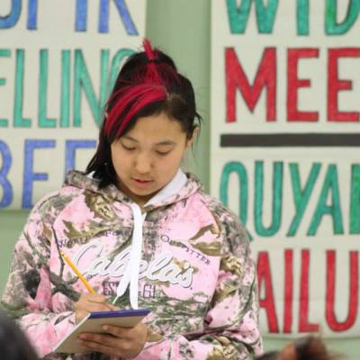 """a young girl writes on a notepad with a pencil, with posters behind her that read """"Spelling Bee"""" and """"Quyana"""""""