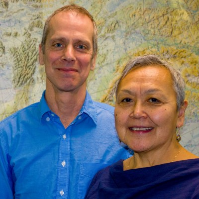 Man and woman stand smiling in front of a large wall map of northwestern Alaska.