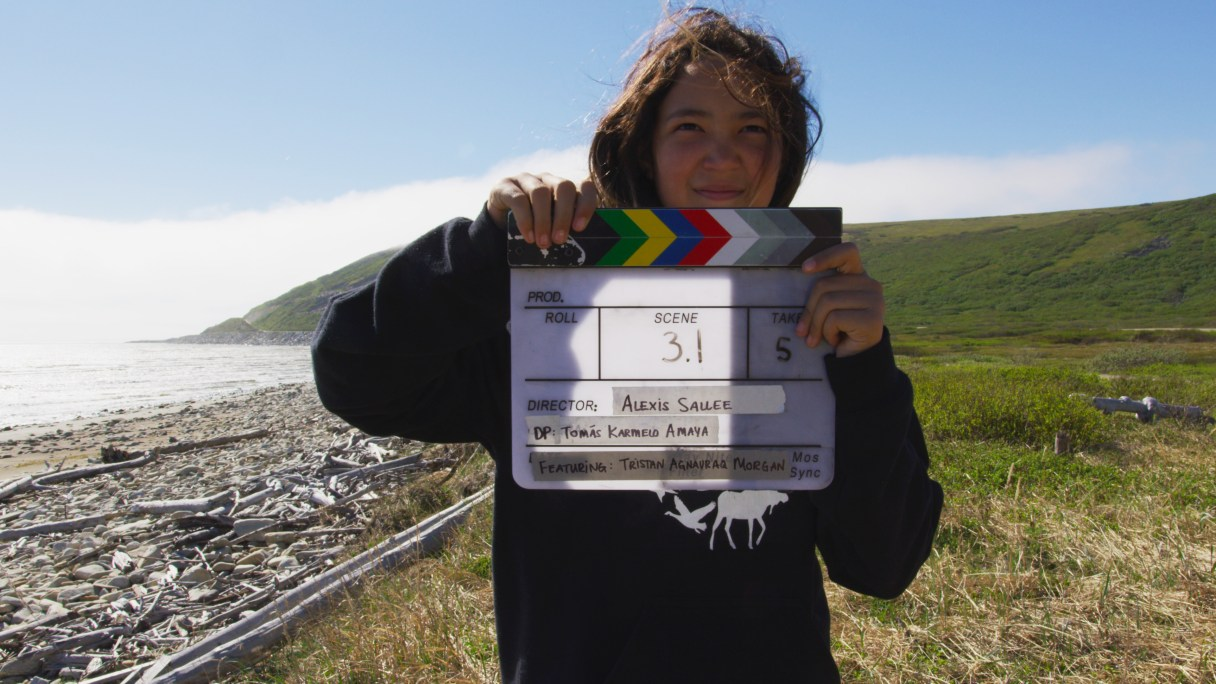 Young woman holds slate for film shoot while standing on rural Alaska seacoast