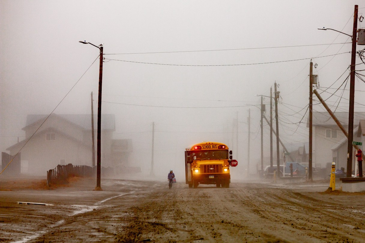 Amid heavy fog, a yellow school bus is stopped in the middle of a dirt road in a rural Alaska town, waiting for a young student to board.