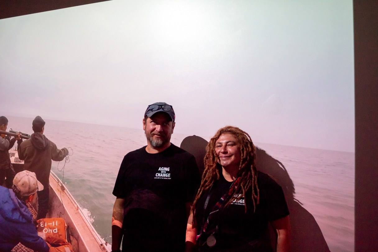 Man and woman stand in front of large screen inside museum exhibit, displaying imagery of traditional marine mammal hunting.