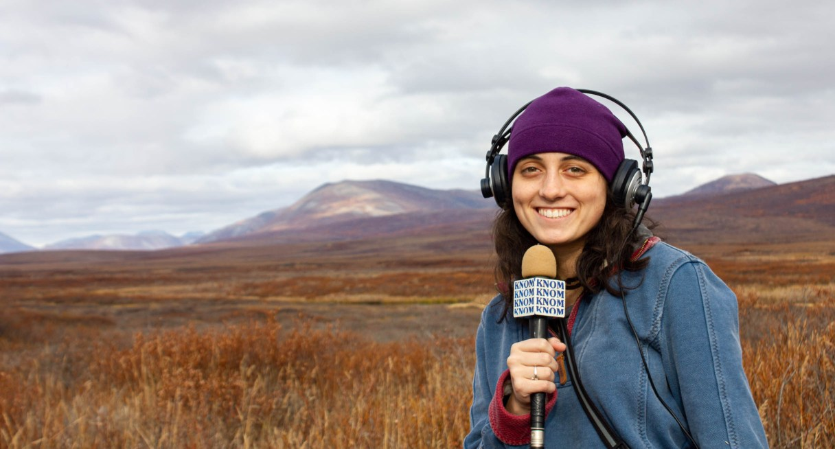 Woman with a microphone standing in front of a mountain range.