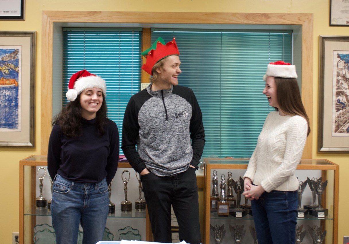 KNOM volunteers: Cathy Rubano, Colin O'Connor, and Sophia DeSalvo in the radio station wearing Christmas hats and laughing.