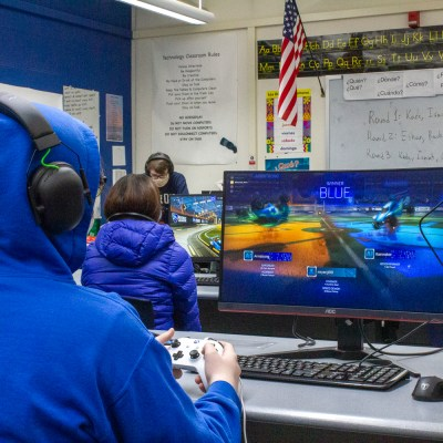 Student in blue hoody sitting at desk with a video game controller playing a game.