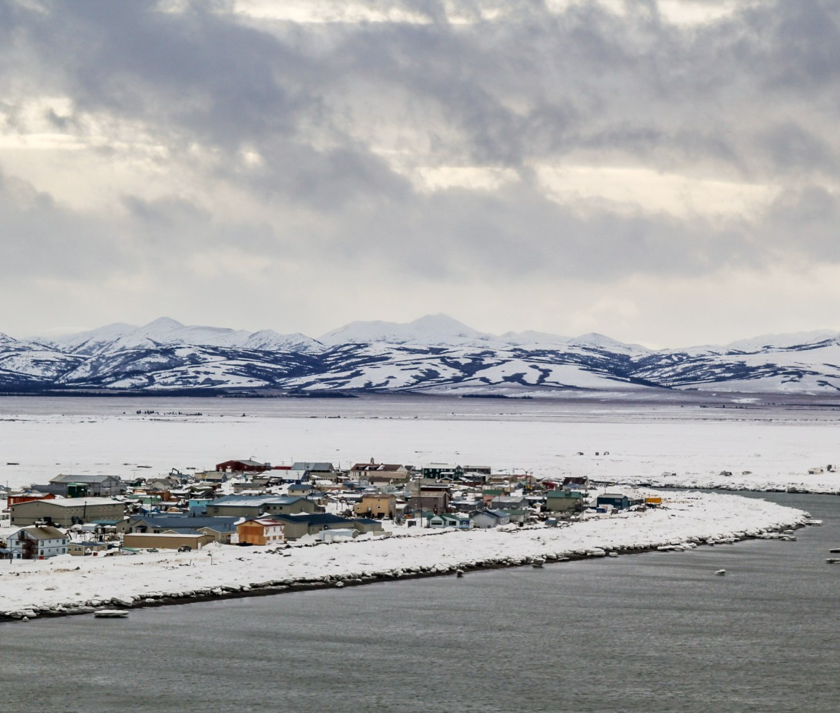Aerial view of Unalakleet. There is mountains in the distance with water in the forefront. Buildings line the coastline. It is winter and snow is covering the ground.