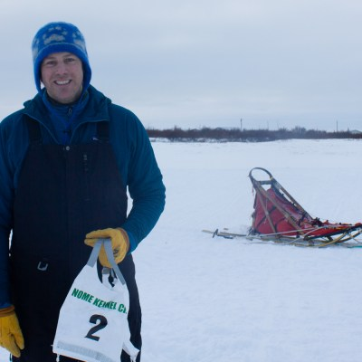 Man holding race bib in the winter time. Dog sled behind him.