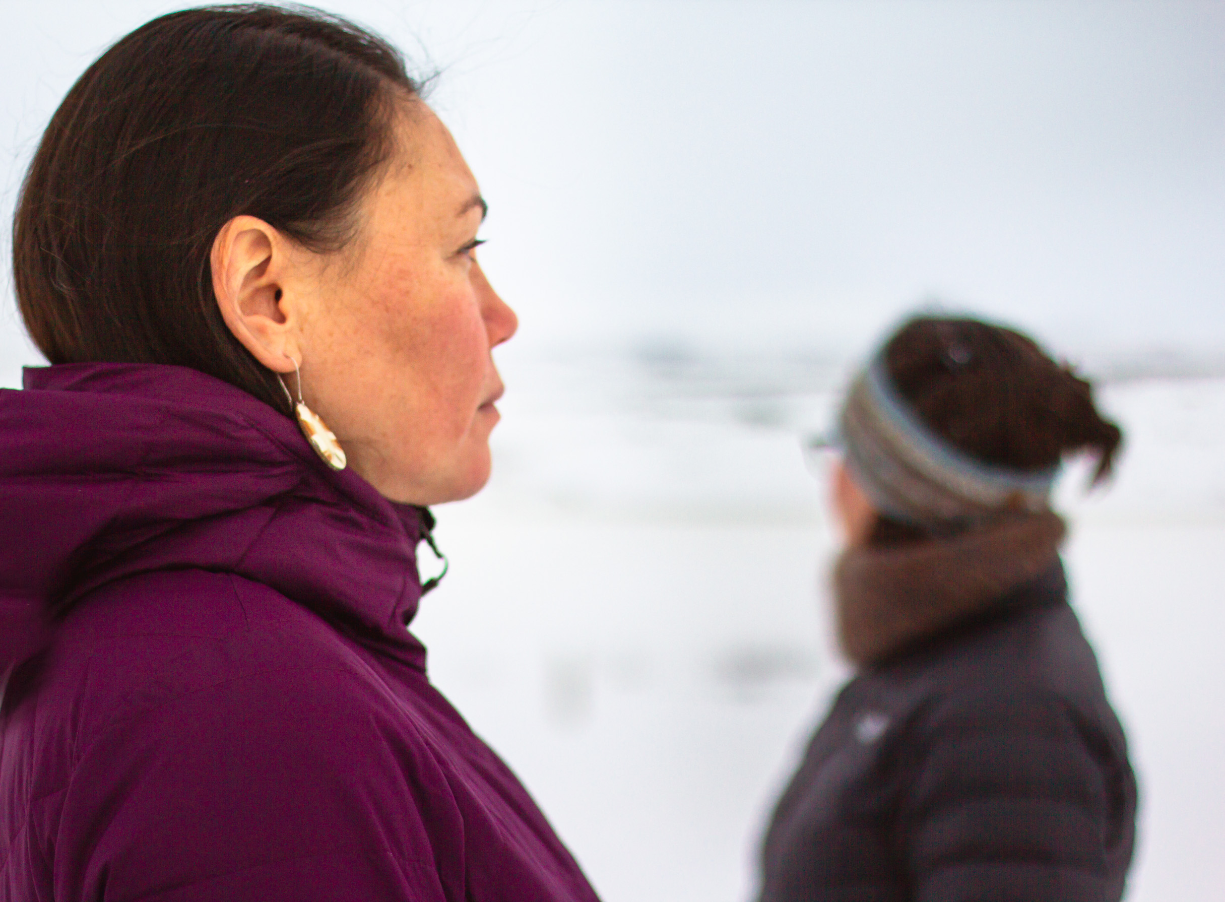 Profile shot of two woman standing outside in the winter time.