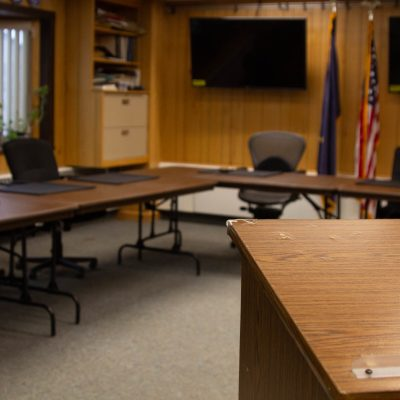 Cirty of Nome council chambers room. View from podium looking towards empty tables with chairs.