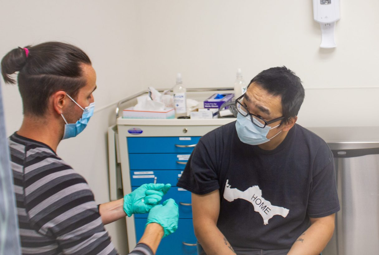 A healthcare worker administering the Covid vaccine to a patient..