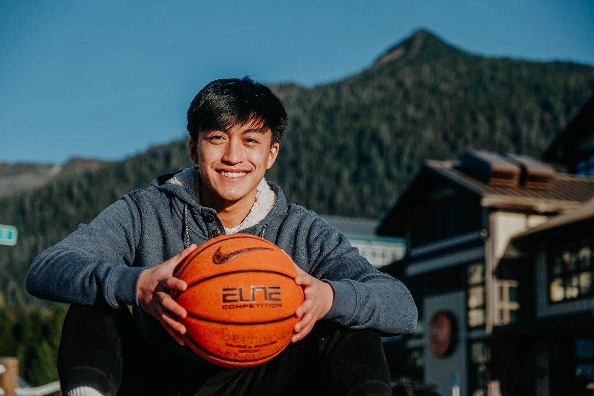 A smiling boy sitting in front with a basketball in his hands. Mountain in the background.