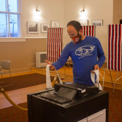 A man wearing a face mask and blue shirt holding up a long piece of paper. He is at a polling booth.