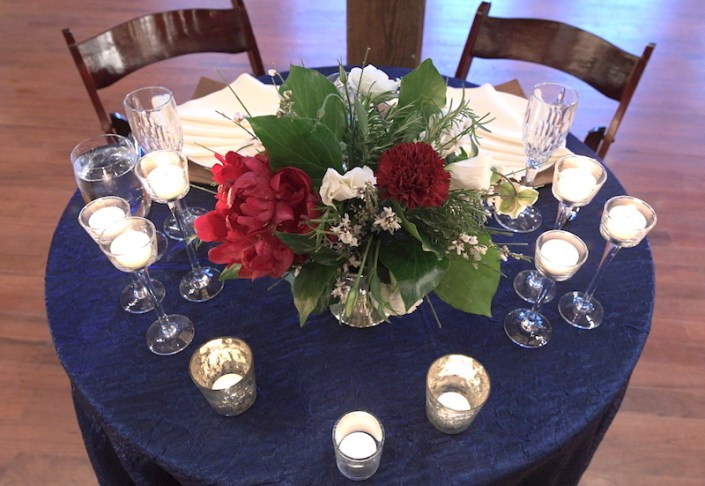 Sweetheart table centerpiece with a red peony