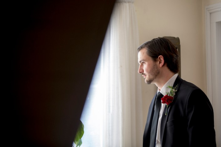 Groom by a window waiting for his bride