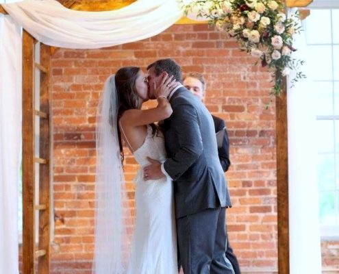 bride and groom kiss under ceremony arbor flowers