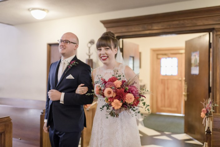 bride and groom enter ceremony with bridal bouquet