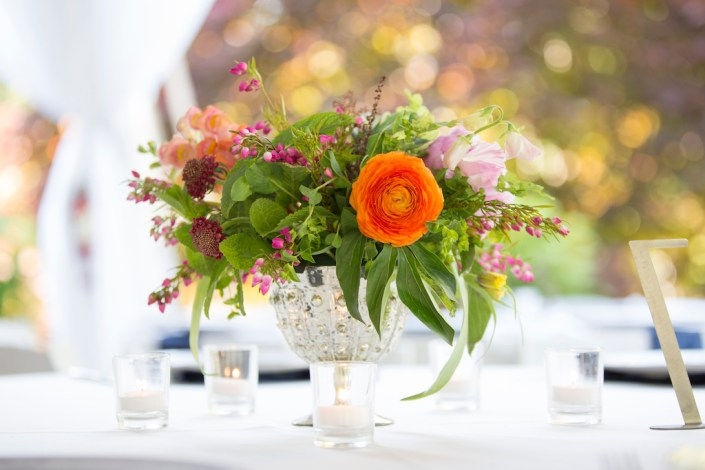 spring flower arrangement with orange ranunculus in a silver compote
