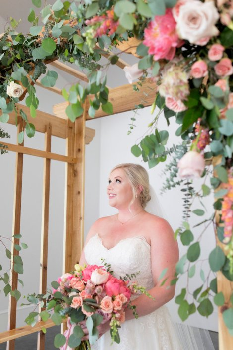 bride-admiring-ceremony-flowers