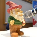 Picture of Knowmo, the KMb Gnome, speaking at a microphone