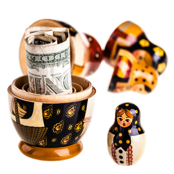 Russian doll with dollars inside isolated on white background