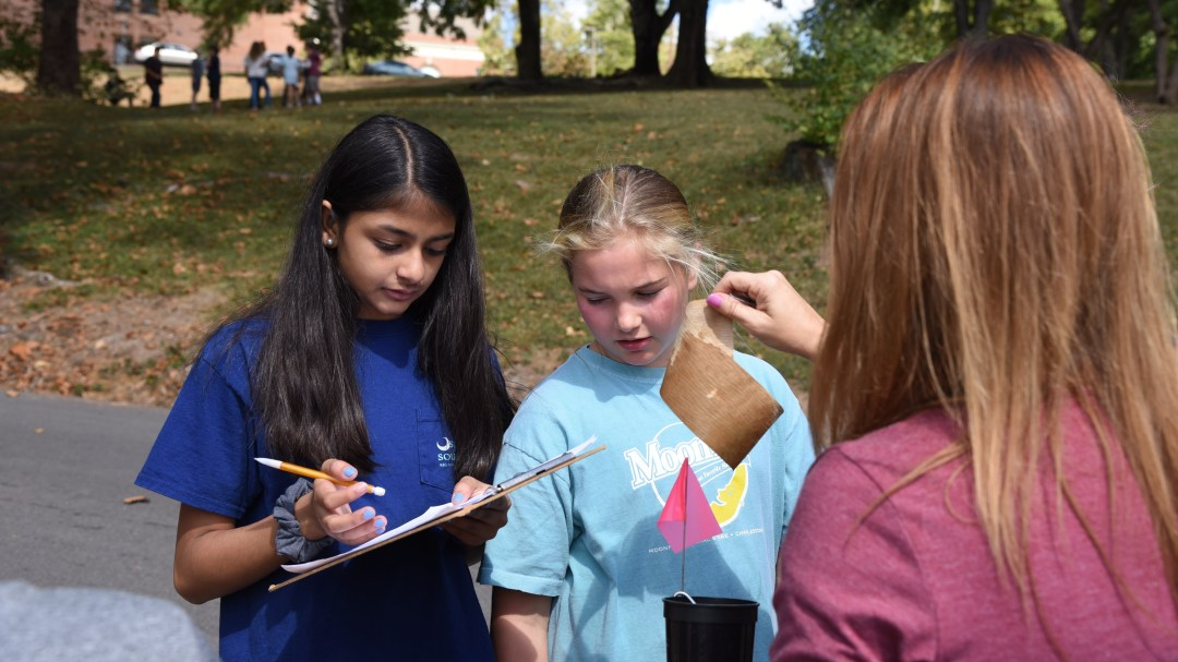 6th-graders Hetvi Patel, left, and Sophia Smelcer record data while Gresham Middle School teacher Nicole Resmondo examines seed germination paper. Students at Gresham are participating in a research study led by the University of Tennessee Institute of Agriculture that aims to promote science careers and to increase understanding of how La Crosse encephalitis is transmitted by mosquitos.