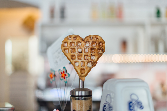 A heart-shaped waffle in focus with a white kitchen wall and shelves in the background.