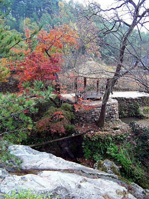 A thatch-roofed pavilion framed by autumn foliage in Soswaemun Gardens in Gwangju, South Korea.
