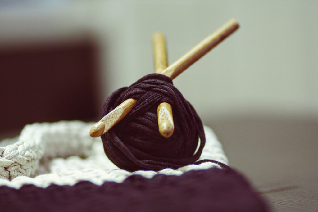 Two wooden crochet hooks stuck in a ball of purple yarn.