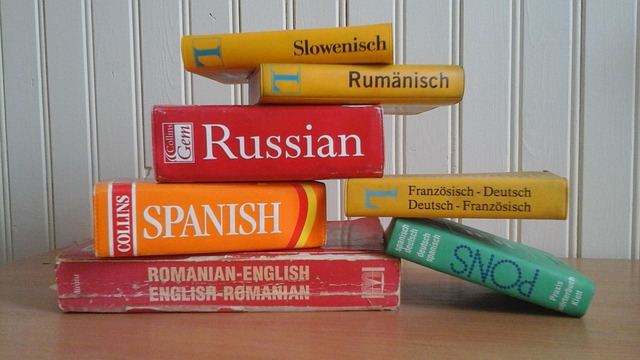 A stack of seven different bilingual dictionaries: Spanish, Russian, Romanian, and Slovenian. They're sitting on a brown table in front of a white clapboard wall.