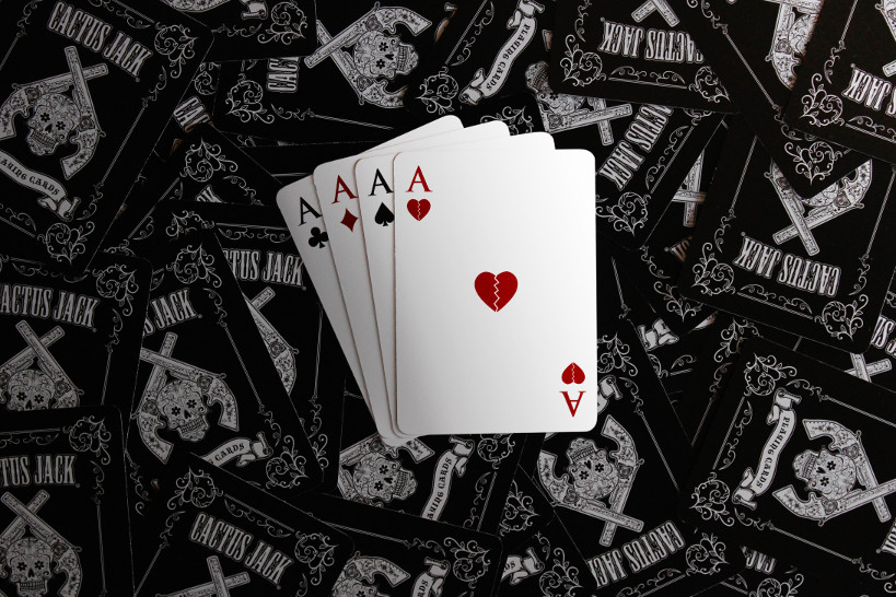 Four aces on a background of black playing card backs with a Wild West motif.