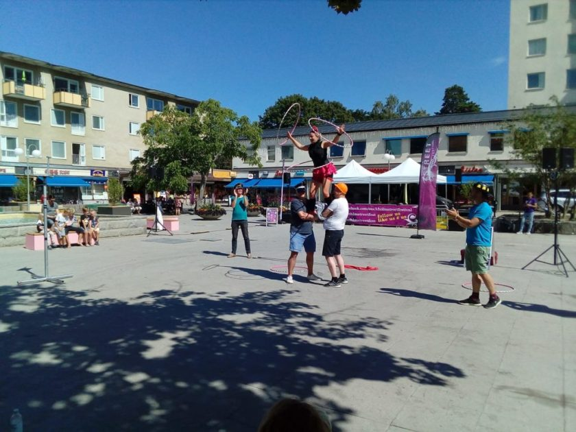 A hula hooping street performer standing on the shoulders of two men, spinning one hoop around her waist and one around each arm.