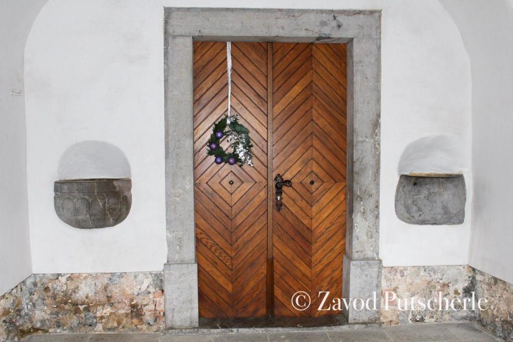 Kropilnik z napisom G. Jon.. ob vhodu v črmošnjiško cerkev.