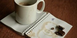 photo of notebook, coffee cup and bits of chocolate candy bar