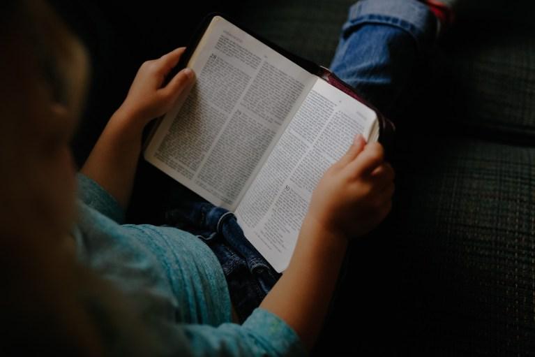 Man sitting reading Bible.