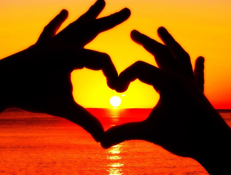 Silhouette of hands making heart shape with fingers at sunset over ocean