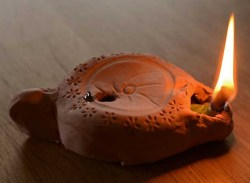 ancient pottery lit oil candle