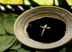 Bowl containing black ashes with a cross laying on the ashes
