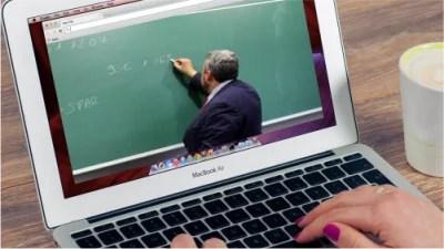 Eine Studentin sieht sich eine virtuelle Vorlesung auf ihrem Notebook an