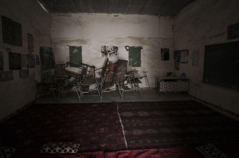 """Cette photos a été prise dans une école primaire. Je me souviens que les enfants étaient en contrôle ce jour-là, ils étaient tous en train d'écrire pendant que les instituteurs surveillaient. J'ai fait le tour de l'école et j'ai vu cette salle vide avec toute ces chaises et ses tables empilées."""" © Adlan Siouxy"""