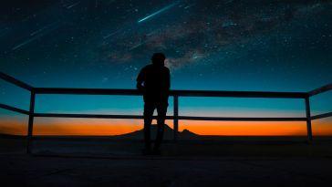 karanlıkta yıldızlara bakan insan