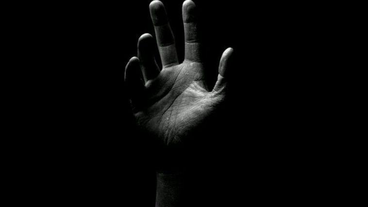 karanlığın içinde yukarı elini uzatan insan