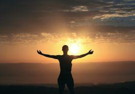 güneşin batışına kollarını açmış insan