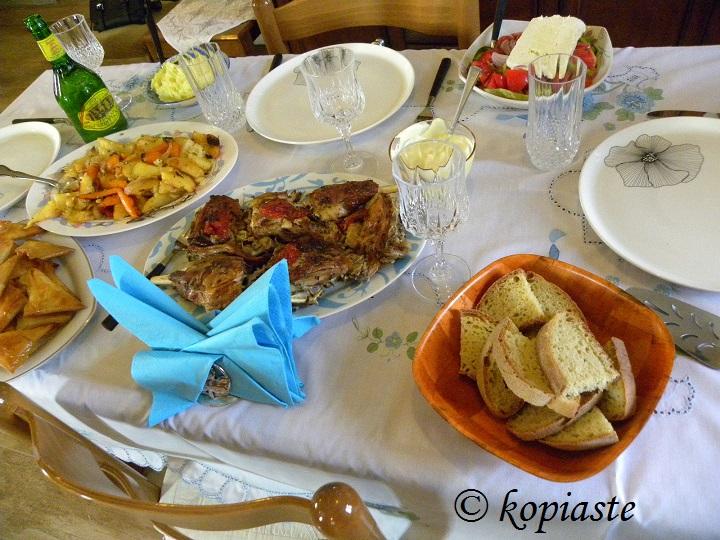 Table set with Kleftiko, roasted potatoes, skordalia, tyropitakia, Greek salad, yoghurt dip image